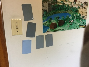 Blue and blue-gray paint samples on a wall.